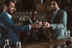 cheerful young male friends in suits clinking glasses of whiskey